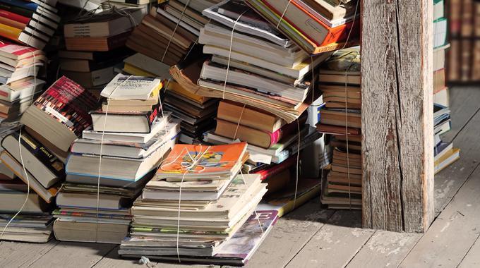 Bücherstapel vor Bücherregalen