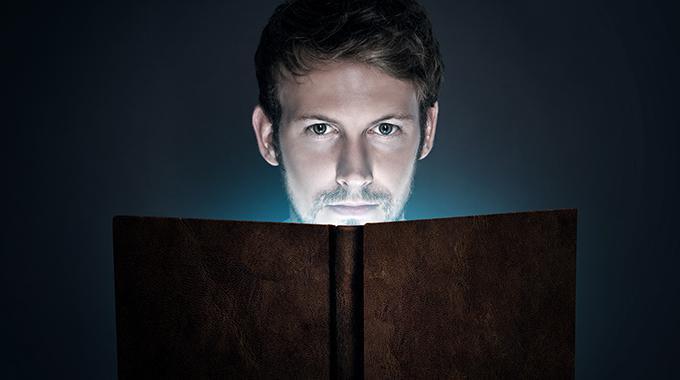 Der gekaufte Bestseller: Mann liest vor dunklem Hintergrund in einem Buch