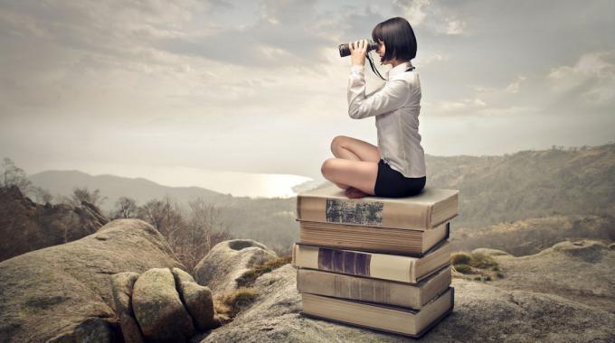 Frau auf Bücherstapel blickt durch ein Vergrößerungsglas in die Ferne